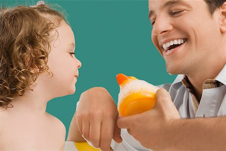 Close-up of a mid adult man looking at his daughter and smiling Stock Photo - Premium Royalty-Free, Code: 625-02267324