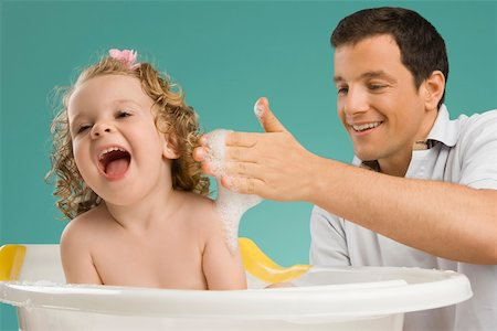 Close-up of a mid adult man giving bath to his daughter Stock Photo - Premium Royalty-Free, Code: 625-02267322