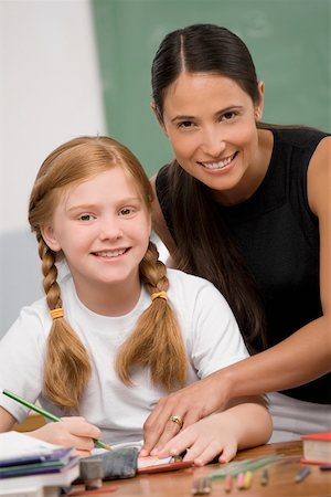 Portrait of a female teacher teaching a schoolgirl in a classroom Stock Photo - Premium Royalty-Free, Code: 625-02267722