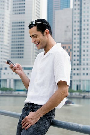 Side profile of a mid adult man text messaging and smiling Stock Photo - Premium Royalty-Free, Code: 625-02267738
