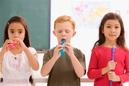 Schoolboy with two schoolgirls playing flutes in a classroom Stock Photo - Premium Royalty-Free, Code: 625-02928938