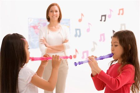 Side profile of two schoolgirls playing flutes with their teacher standing in the background Stock Photo - Premium Royalty-Free, Code: 625-02928945