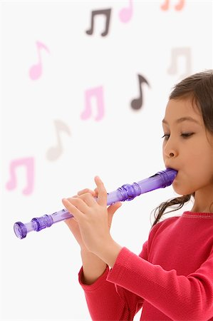 Side profile of a schoolgirl playing a flute in a classroom Stock Photo - Premium Royalty-Free, Code: 625-02928975