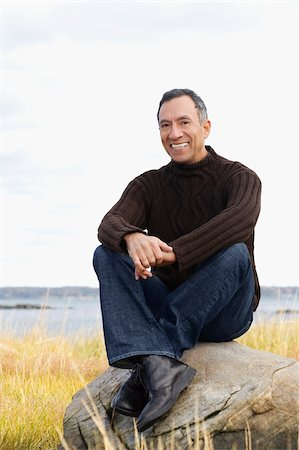 Portrait of a mature man sitting on a rock and smiling Stock Photo - Premium Royalty-Free, Code: 625-02930285
