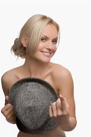 Portrait of a young woman covering her breast with a hat and smiling Stock Photo - Premium Royalty-Free, Code: 625-02930684