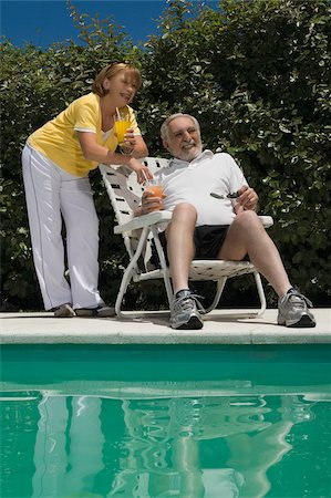 Senior couple holding glasses of juice at the poolside Stock Photo - Premium Royalty-Free, Code: 625-02931093
