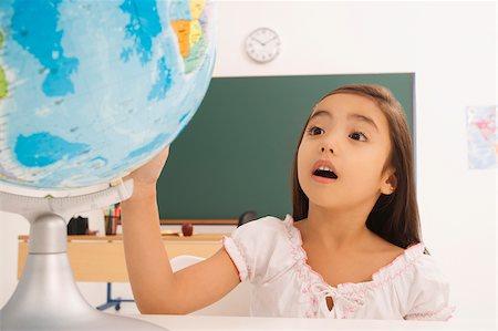 Girl looking at a desktop globe Stock Photo - Premium Royalty-Free, Code: 625-02931726