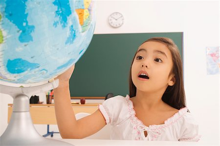 Girl looking at a desktop globe Stock Photo - Premium Royalty-Free, Code: 625-02931726