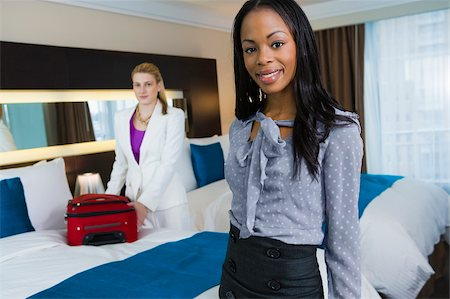 Portrait of a businesswoman smiling with another businesswoman packing her luggage Stock Photo - Premium Royalty-Free, Code: 625-02931998
