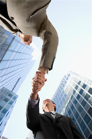 Low angle view of two businessmen shaking hands and smiling Stock Photo - Premium Royalty-Free, Code: 625-02932235