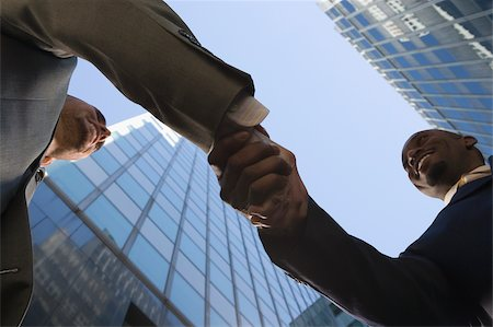 Low angle view of two businessmen shaking hands and smiling Stock Photo - Premium Royalty-Free, Code: 625-02932939