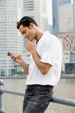 Side profile of a mid adult man text messaging and smiling Stock Photo - Premium Royalty-Free, Code: 625-02933176