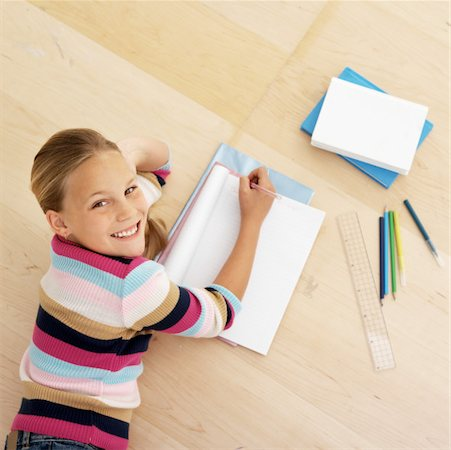preteen  smile  one  alone - Elevated view of girl lying on floor and doing homework (10-11) Stock Photo - Premium Royalty-Free, Code: 627-00855568
