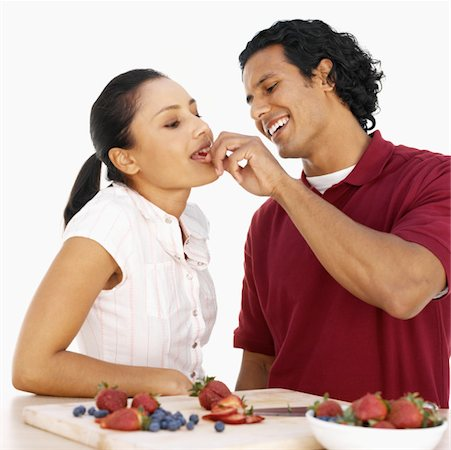 Close-up side view of young man feeding young woman strawberry Stock Photo - Premium Royalty-Free, Code: 627-00856261