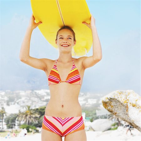 Front view portrait of young woman holding surfboard over her head Stock Photo - Premium Royalty-Free, Code: 627-00856619