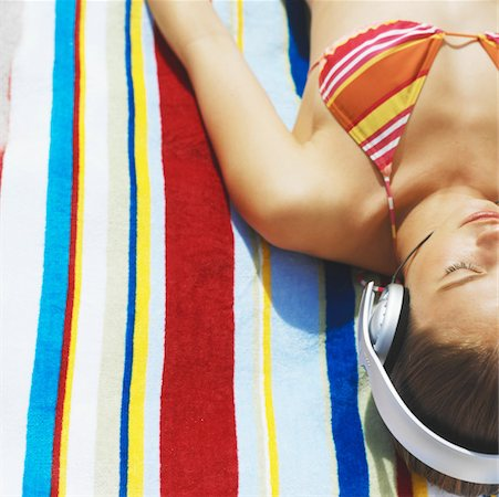 Elevated view of young woman lying on a towel wearing headphones Stock Photo - Premium Royalty-Free, Code: 627-00856611