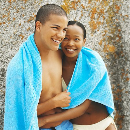 Close-up of young couple with arms around each other and holding towel between them Stock Photo - Premium Royalty-Free, Code: 627-00856627