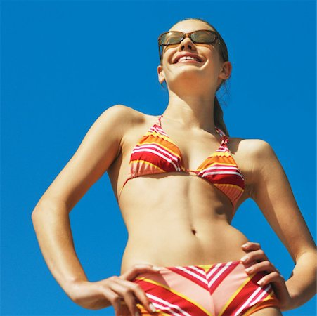 Close-up front view of young woman wearing bikini with hands on hips Stock Photo - Premium Royalty-Free, Code: 627-00856636