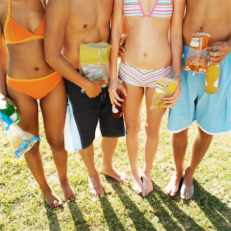 Front view low section of four young people holding crisps and soda Stock Photo - Premium Royalty-Free, Code: 627-00856651