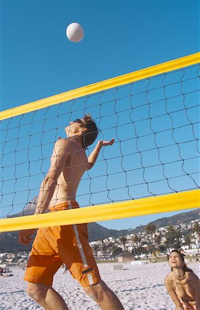 Low angle view of a young man playing volleyball on the beach Stock Photo - Premium Royalty-Free, Code: 627-00856775