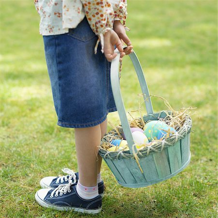 Girl (6-7) with a basket of Easter eggs Stock Photo - Premium Royalty-Free, Code: 627-00857194