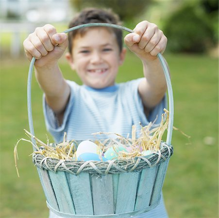Boy (7-8) holding up a basket of Easter eggs Stock Photo - Premium Royalty-Free, Code: 627-00857195
