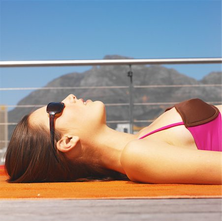 Close-up side view of young woman sunbathing Stock Photo - Premium Royalty-Free, Code: 627-00852987