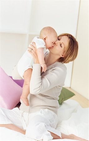 daughter kissing mother - Close-up of mother holding baby girl (6-12 months) sitting on bed Stock Photo - Premium Royalty-Free, Code: 627-00853111