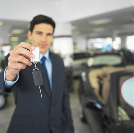 Portrait of a salesman holding out a car key Stock Photo - Premium Royalty-Free, Code: 627-00861197