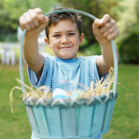 Boy (7-8) holding up a basket of Easter eggs Stock Photo - Premium Royalty-Free, Code: 627-00862284