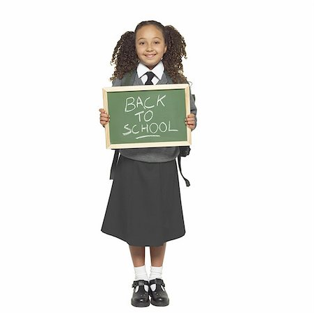 preteen  smile  one  alone - Portrait of a girl (11-12) wearing her school uniform holding  a chalk board Stock Photo - Premium Royalty-Free, Code: 627-01063117