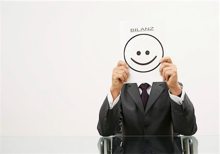 """results - Businessman holding a piece of paper in front of his face with a smiley on it and letters saying """"Bilanz"""" Stock Photo - Premium Royalty-Free, Code: 628-05817414"""