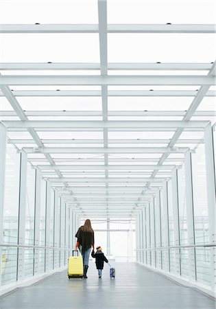 Mother and son walking with baggage through a passage, Munich airport, Bavaria, Germany Stock Photo - Premium Royalty-Free, Code: 628-05817425