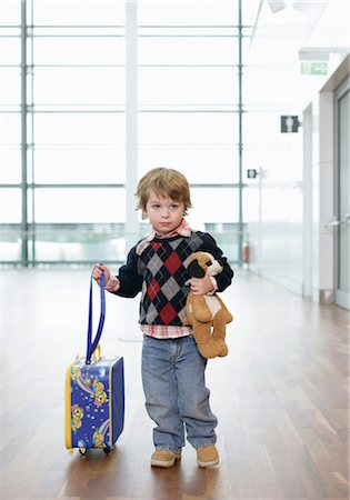 A shy boy with a soft toy and a trolley on an airport Stock Photo - Premium Royalty-Free, Code: 628-05817426