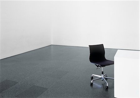 Office chair and desk in an empty room Stock Photo - Premium Royalty-Free, Code: 628-05817457