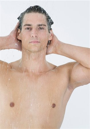 Young man taking a shower Stock Photo - Premium Royalty-Free, Code: 628-05817544