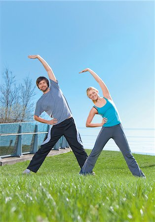 Man and woman doing gymnastics in meadow Stock Photo - Premium Royalty-Free, Code: 628-05817584