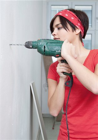 Young woman drilling with electric drill Stock Photo - Premium Royalty-Free, Code: 628-05817628