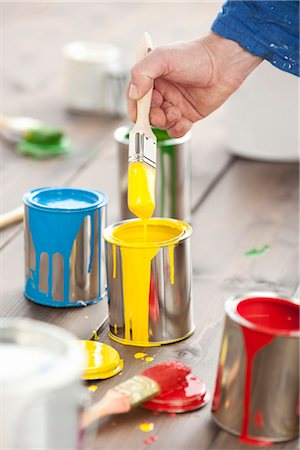 spot paint - Hand with paintbrush and multicolored paint cans Stock Photo - Premium Royalty-Free, Code: 628-05817698