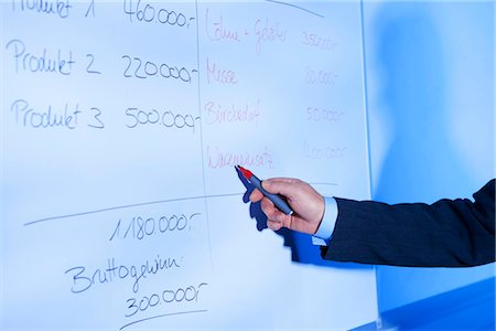 Businessman calculating on whiteboard Stock Photo - Premium Royalty-Free, Code: 628-05817692