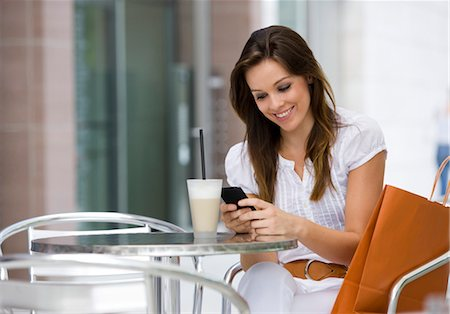 europe coffee shop - Happy woman with cell phone at outdoor cafe Stock Photo - Premium Royalty-Free, Code: 628-05817740