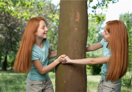 red hair preteen girl - Red haired female twins surrounding a tree Stock Photo - Premium Royalty-Free, Code: 628-05817765
