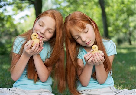 red hair preteen girl - Red haired twins holding chicks Stock Photo - Premium Royalty-Free, Code: 628-05817766