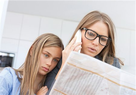 Mother reading newspaper and phoning with daughter by her side Stock Photo - Premium Royalty-Free, Code: 628-05817770