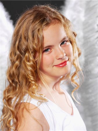 Girl with curly hair wearing angel wings Stock Photo - Premium Royalty-Free, Code: 628-05817795