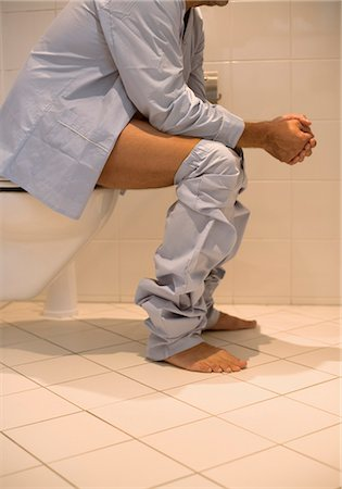 Man wearing pajamas on toilet Stock Photo - Premium Royalty-Free, Code: 628-05817987