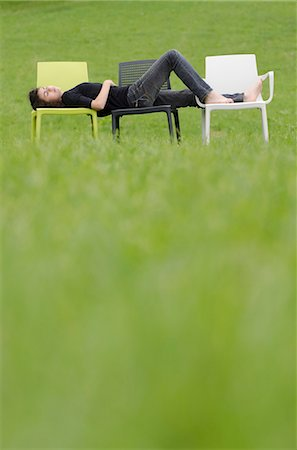Girl sleeping on plastic chairs in meadow Stock Photo - Premium Royalty-Free, Code: 628-07072121