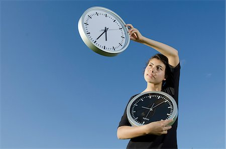 Girl holding clocks outdoors Stock Photo - Premium Royalty-Free, Code: 628-07072133