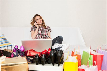 person on phone with credit card - Young woman with cell phone and laptop on couch surrounded by shopping bags and new shoes Stock Photo - Premium Royalty-Free, Code: 628-07072265