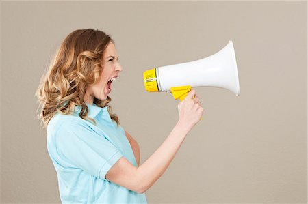 Young woman screaming into megaphone Stock Photo - Premium Royalty-Free, Code: 628-07072273